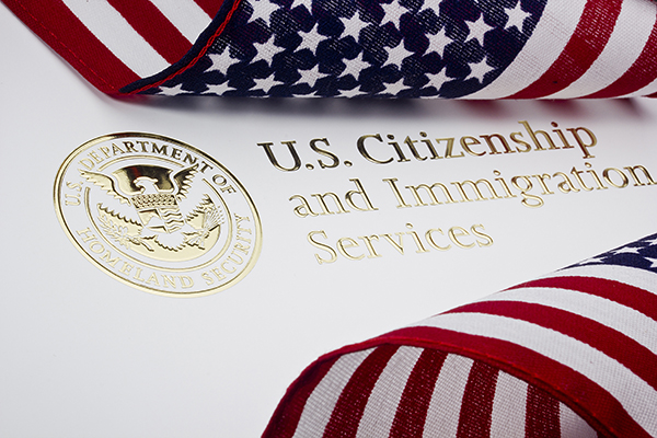 Gold seal stamped onto white paper for U.S. Citizenship and Immigration Services surrounded by billowing United States flags