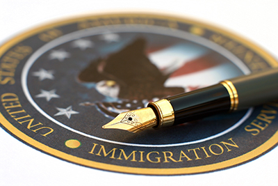 Official Seal of the United States Citizenship and Immigration Services (USCIS) with a brass fountain pen