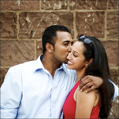 Immigrant man kissing his smiling fiance on the cheek