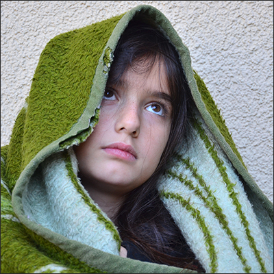 Little refugee girl looking forlorn and wrapped in an old green blanket